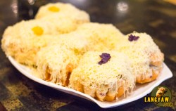A dish of ensaimada of different flavors densely covered with cheddar cheese