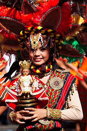 A dancer in her elaborate finery holding the image of the Sto. Nino