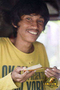 A man happily posing after taking a bite of the kakanin