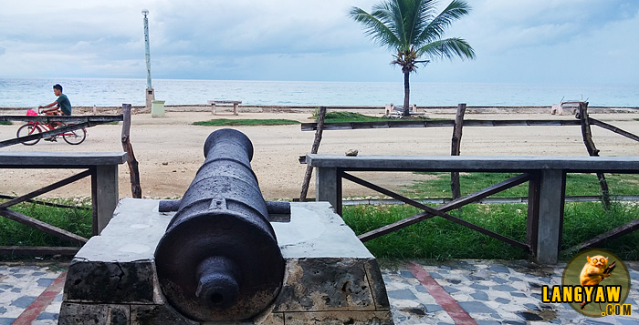 Cannon facing the sea that is mounted infront of a century old watchtower