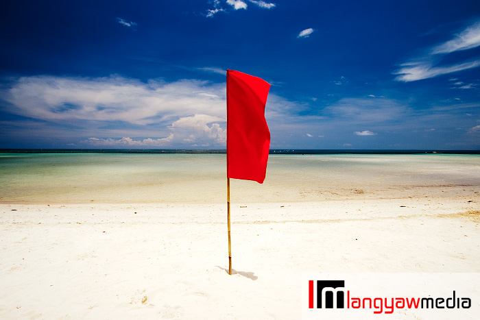 Red flag stand guard at the white sand beach