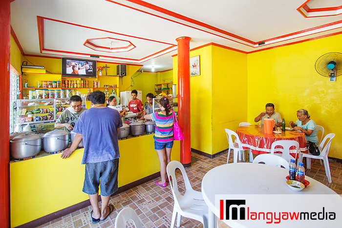 Interior of the carinderia with its cheerful yellow painted wall and red accents