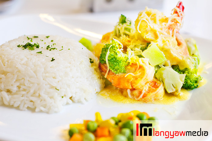 Shrimp thermidore with broccoli florets, broccoli stems and cauliflower and grated with cheese