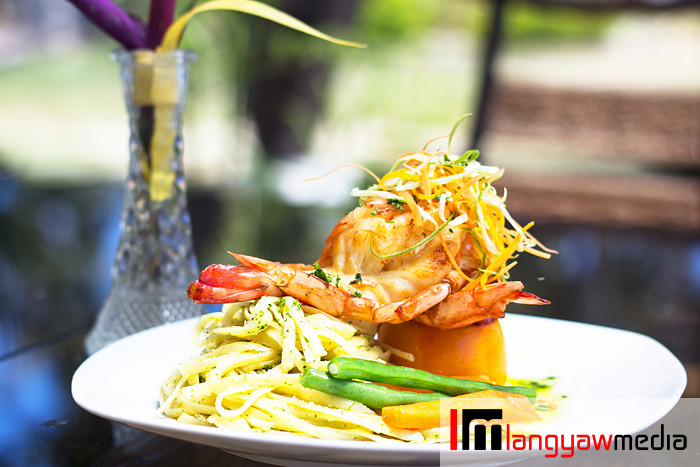 Boracay grilled prawns with pasta: prawns, buttered veggies with olive oil and tomatoes topped with julliened orange rind skin as garnish. Pasta with malunggay pesto and light cream for sauce.