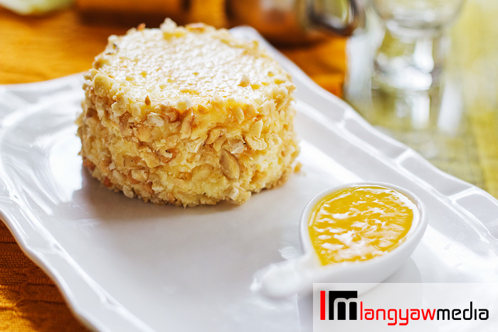 Baked cheesecake covered with peanuts and paired with fresh mango puree. It's a delightful combo!