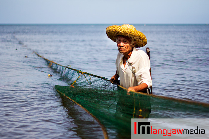 An old fisherman pulling his net early in the afternoon at the beach in Dapitan City, Zamboanga del Norte