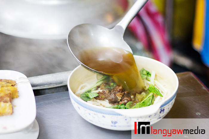 An order of beef noodle soup being readied