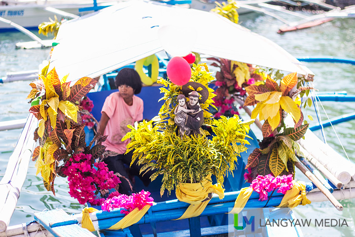 A motorized outrigger boat bedecked with flowers and an image of St. Anthony of Padua