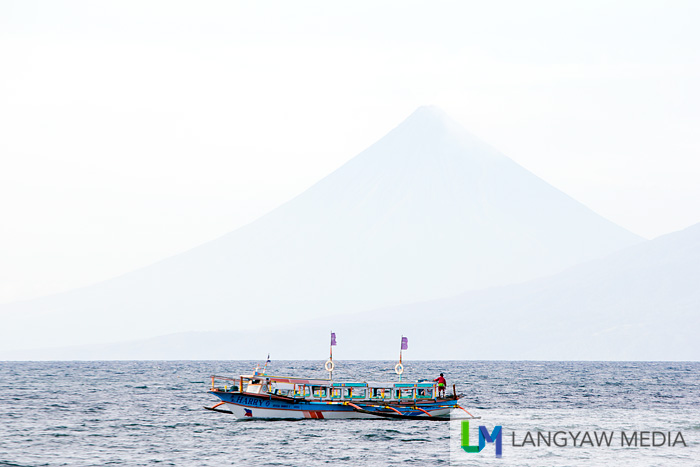 Beautiful Mt. Mayon in the distance as an outrigger boat passes by Sabang