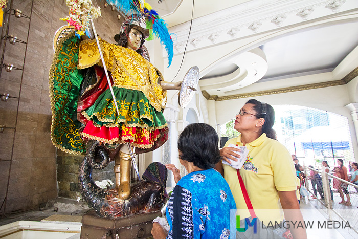A devotee touches the image with her handkerchief and presses it on her chest