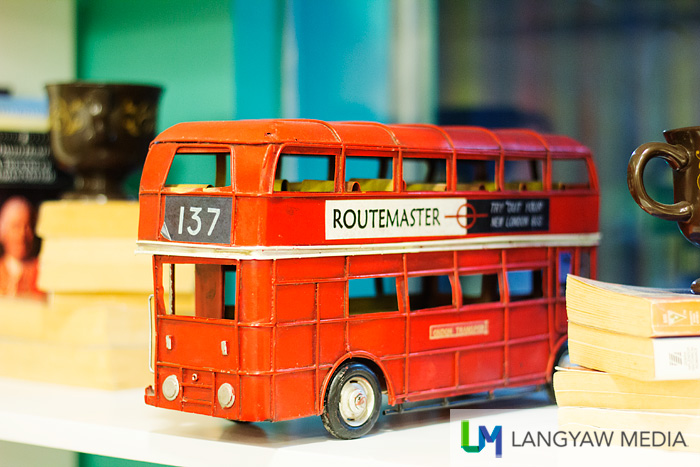 A toy double decker bus as decor in one of the shelves