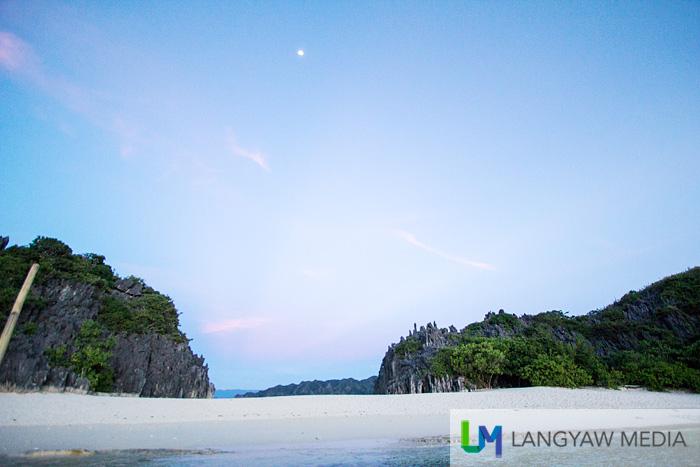A moon shine, blue sky, dusk and fine white sand