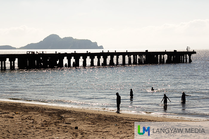 The old and dilapidated wharf of South beach with bathers in the foreground and Caballo Island in the background.