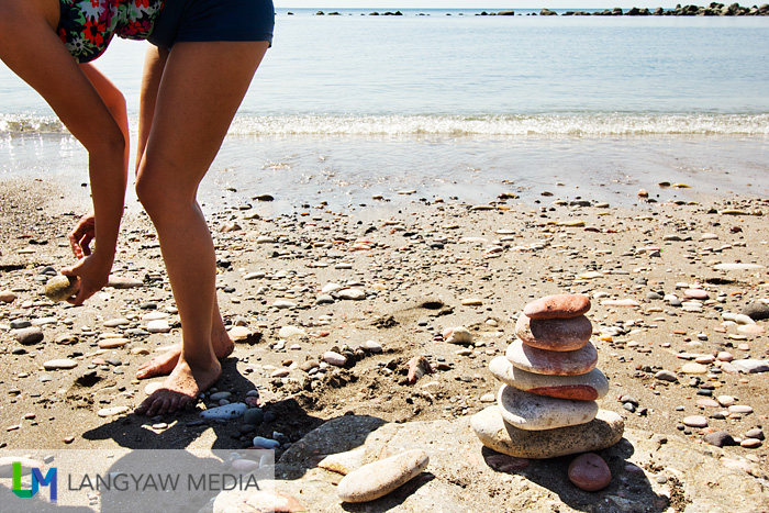 A visitor looks for smooth round rocks to complete her pile
