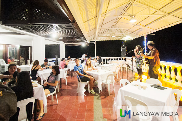 The al fresco dining area of Corregidor Inn at night with live performers