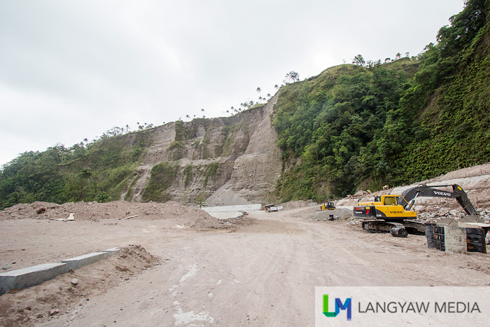 A road cuts through the mountains and forests and so close to Tuasan Falls