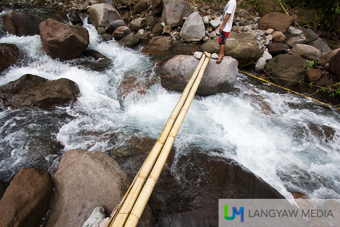 You need to pass through this thin pole of bamboo to cross the river