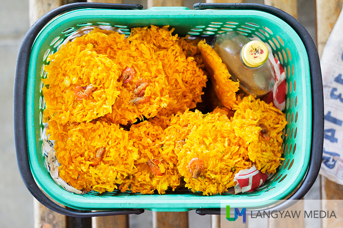 The vendor's basket filled with okoy and a bottle of langgaw, or vinegar