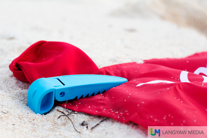 Close up of the beach blanket clip. It's teeth grips the towel to the sand.