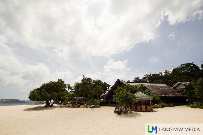 The low buildings surrounded with trees, vegetation, white sand and the eternally aquamarine waters of the sea