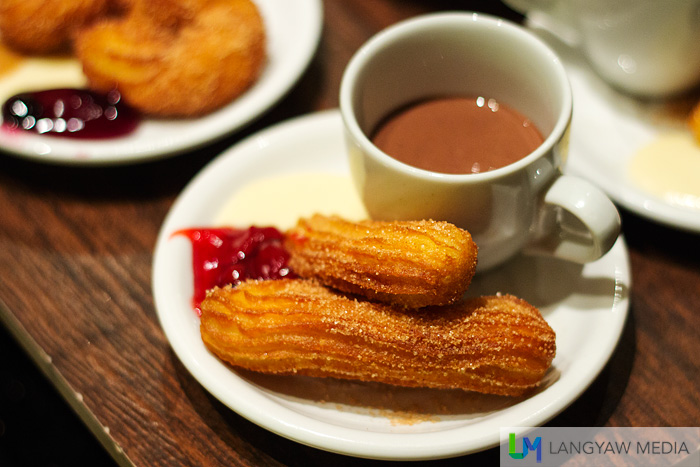 crisp churros with hot thick chocolate and sweet cream with strawberry jam