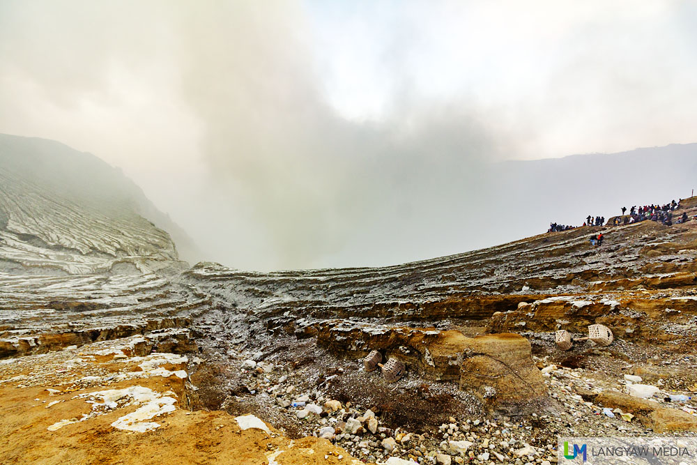 A portion of the crater at Kawah Ijen as volcanic smoke emanates from below