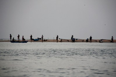 Fishermen line the shores of Batticaloa lagoon at dusk
