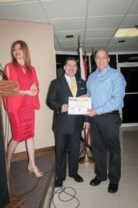 El escritor Fernando Almanzar recibe de Carlos Montes de Oca su reconocimiento como finalista del concurso.