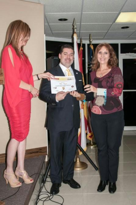 La escritora Mila Hajjar recibe reconocimiento de Carlos Montes de Oca como finalista del concurso.
