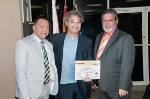 El escritor Noel Morgado-Santos, recibe su reconocimiento como ganador del quinto lugar por parte del Rector del Sistema Educativo Ana G Méndez, Luis Burgos y de Derick Toro, presidente de Family Life Care Services.
