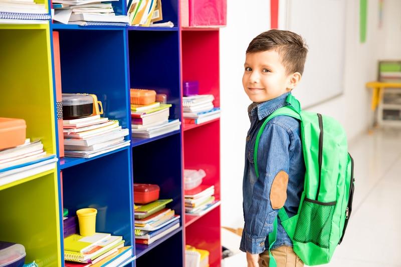 Niño pequeño con una mochila sonriendo