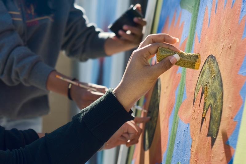 jóvenes pintando en un mural.