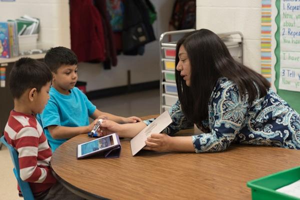 Una maestra enseñando a dos niños en una tableta.