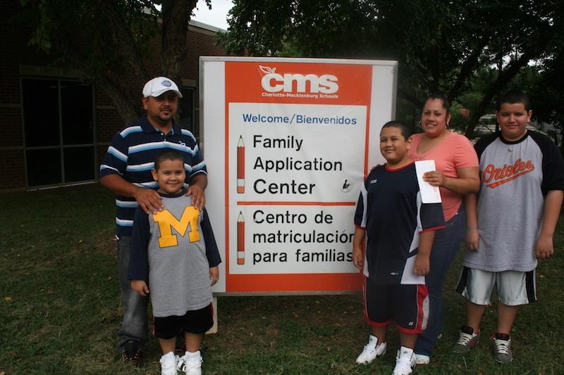 Familia enfrente de pancarta del sistema escolar de Mecklenburg.