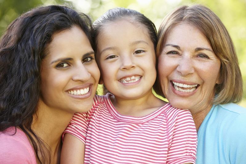 Foto de una niña con su mamá y abuela.