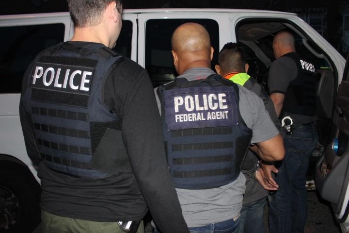 Dos oficinales de espaldas arrestando un inmigrante.