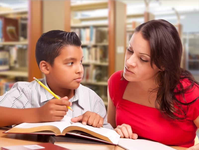 Mujer ayudando a un niño a estudiar