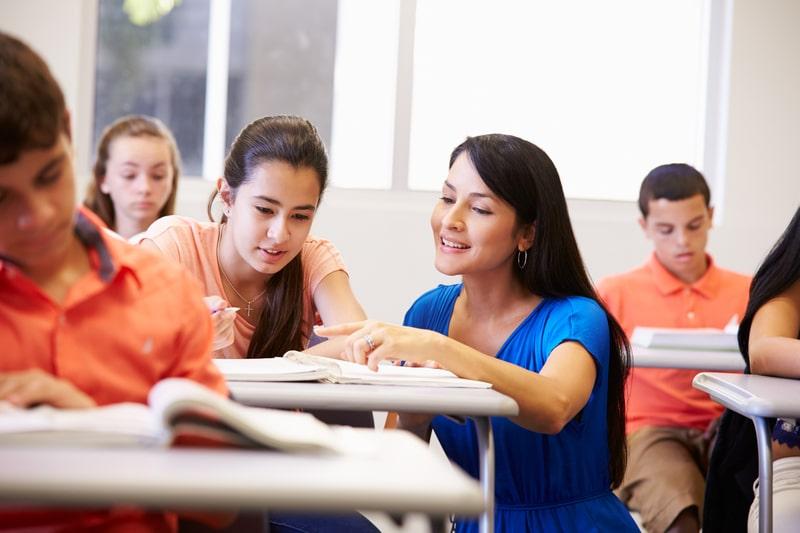 maestra ayudando a estudiante en una clase