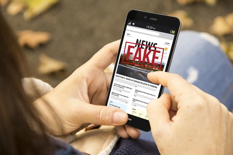 Una mujer sosteniendo un telefono con la pantalla que dice: noticias falsas