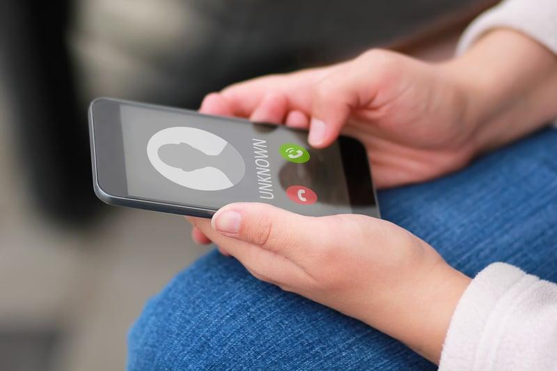 Una persona sosteniendo un telefono en sus manos