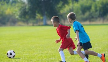 Dos niños jugando fútbol