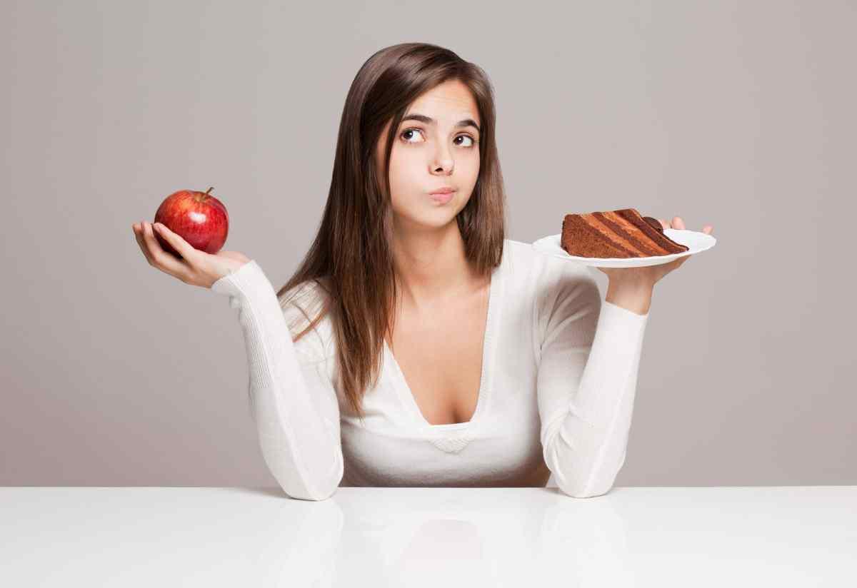 Una mujer decidiendo entre una manzana y una rebanada de pastel