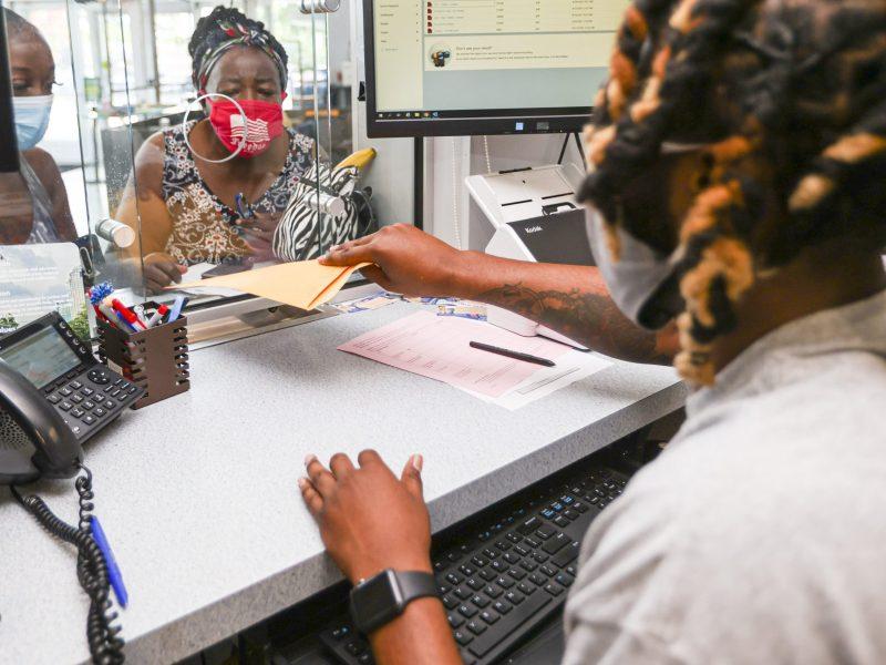 Hattie Howie, centro, habla con Lawrence Winston, representante de servicio al cliente de Crisis Assistance Ministry en Spratt Street en Charlotte, el jueves 1ro de julio del 2021. / Foto de Nell Redmond para el Charlotte Journalism Collaborative.