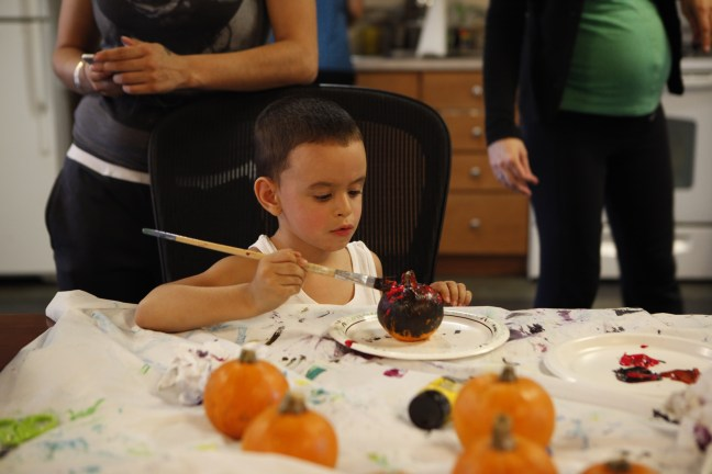 A child paints a pumpkin as part of a Halloween-themed art group at Lantern's Jasper Hall in the Bronx