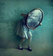 nina-sosteniendo-el-espejo-de-su-cabeza-en-mitad-de-habitacion-difuminada-001