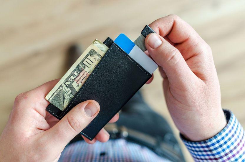 person holding black card holder 928181 - Estudio asegura que eliminar ayudas por desempleo no ayudará a cubrir vacantes