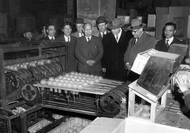Para ahli pelatihan industri mengawasi sebuah mesin bola lampu menjatuhkan bohlam pada pekerja lain yang menyortirnya berdasarkan cacat atau kerusakan bohlam tersebut, di Tokyo Shibaura Electric Co. , kota Tokyo, 25 Januari 1951. (Photo by Arthur Curlis/AP Photo/U.S. Army via The Atlantic)
