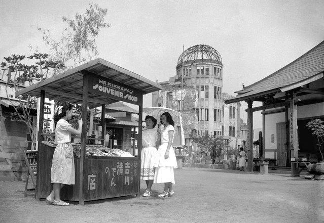 Pada 3 Agustus 1951, yaitu enam tahun setelah bom atom dijatuhkan tepat di atas titik ini di Hiroshima, sebuah kios cenderamata berdiri di jalan dekat kubah Balai Industri yang hancur. Kios ini dioperasikan oleh Kiyoshi Yoshikawa, yang juga terluka dalam peristiwa pengeboman tersebut. (Photo by AP Photo/Kyodo via The Atlantic)