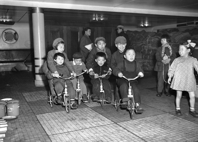 Anak-anak dari keluarga Jepang yang dipulangkan ke negaranya ini bersenang-senang dengan sepedanya di atas dek Kapal Koan Maru selagi orangtua mereka bersiap untuk turun dari kapal di Teluk Maizuru, Jepang, 24 Maret 1953. Kelompok pertama yang dipulangkan dari China dimana mereka terdampar sejak akhir perang dunia kedua ini telah melengkapi formalitas di pusat pemrosesan di Maizuru dan diperbolehkan pulang ke rumah. Gelombang pertama ini terdiri dari 2000 orang pria, wanita dan anak-anak yang datang dari China Utara menaiki kapal Koan Maru ini. Sepeda yang mereka naiki adalah pemberian dari beberapa organisasi amal dan ditempatkan di atas kapal ketika kapal ini meninggalkan China. (Photo by Y. Jackson Ishizaki/AP Photo via The Atlantic)