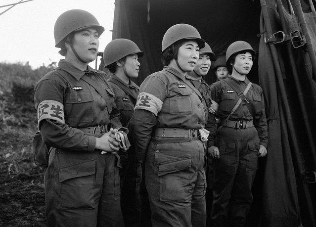 """Para wanita perawat dari pasukan Bela Diri Jepang yang baru dibentuk, di Hokkaido, Jepang, dalam sebuah latihan perang pada 20 Oktober 1955. Pasukan Jepang, menggunakan peralatan yang disuplai oleh Amerika Serikat melakukan latihan militer pertama kalinya setelah perang dunia dengan sebuah kelompok pengawas dari Amerika Serikat dan pengawas militer dari negara asing lainnya, dalam sebuah skenario pertahanan melawan """"musuh bayangan"""" yang menginvasi kepulauan Jepang. (Photo by AP Photo via The Atlantic)"""